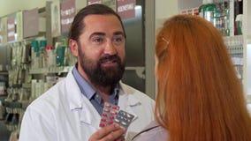 Farmacéutico de sexo masculino amistoso que vende píldoras al cliente femenino almacen de metraje de vídeo