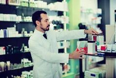 Farmacéutico de sexo masculino que busca la medicina correcta Imágenes de archivo libres de regalías