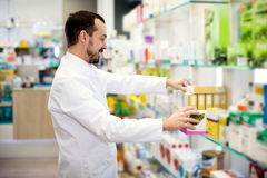 Farmacéutico de sexo masculino que busca para la droga confiable foto de archivo libre de regalías