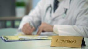 Farmacéutico de sexo masculino que completa la documentación médica, medicamentos de venta con receta, farmacia almacen de video