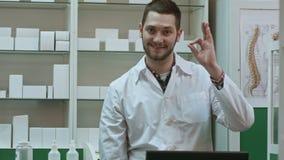 Farmacéutico de sexo masculino sonriente en la capa blanca que muestra los pulgares para arriba y gesto de manos del okey metrajes