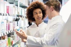 Farmacéutico dedicado que habla con el colega sobre cualidades de la nueva medicina imagenes de archivo