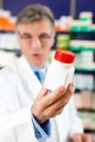 Farmacéutico en farmacia con el medicamento fotografía de archivo libre de regalías