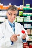 Farmacéutico en farmacia con el medicamento foto de archivo libre de regalías