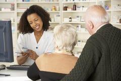 Farmacéutico en farmacia con los pares mayores Imagen de archivo libre de regalías