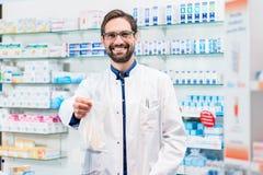 Farmacéutico en la farmacia que vende los productos farmacéuticos en bolso fotografía de archivo libre de regalías