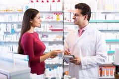 Farmacéutico experimentado que aconseja al cliente femenino imágenes de archivo libres de regalías