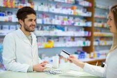 Farmacéutico experimentado que aconseja al cliente femenino imagen de archivo