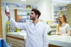 Farmacéutico experimentado que aconseja al cliente femenino en farmacia imagenes de archivo