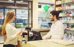 Farmacéutico experimentado que aconseja al cliente femenino en farmacia imagen de archivo