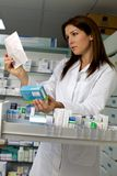 Farmacéutico hermoso de la mujer que busca la medicina con la prescripción Imagen de archivo