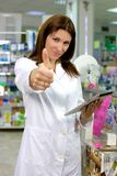 Farmacéutico hermoso en pulgar de la farmacia para arriba Imagenes de archivo