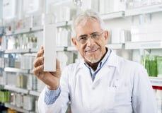 Farmacéutico mayor confiado Holding Medicine Box en farmacia Imágenes de archivo libres de regalías