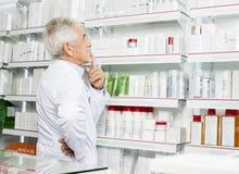 Farmacéutico mayor pensativo Looking At Shelves fotografía de archivo libre de regalías