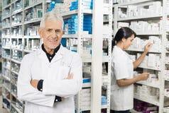 Farmacéutico mayor Standing Arms Crossed mientras que comprobación del colega Imagenes de archivo