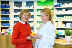 Farmacéutico que da los medicamentos de venta con receta del cliente Imagen de archivo libre de regalías