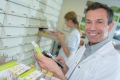 Farmacéutico que examina la acción médica Imagenes de archivo