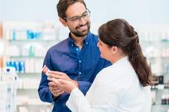 Farmacéutico que habla con el cliente en farmacia fotos de archivo libres de regalías