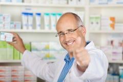 Farmacéutico que muestra los pulgares para arriba Imagen de archivo libre de regalías