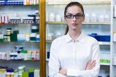 Farmacéutico que se coloca con los brazos cruzados en farmacia Imágenes de archivo libres de regalías