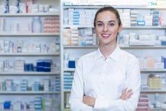 Farmacéutico que se coloca con los brazos cruzados en farmacia Imagen de archivo