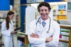 Farmacéutico que se coloca con los brazos cruzados en farmacia Fotografía de archivo libre de regalías