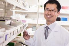 Farmacéutico que toma abajo y medicación de examen de la prescripción en una farmacia, mirando la cámara Imagen de archivo libre de regalías