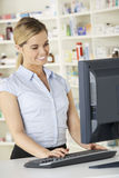 Farmacéutico que trabaja en el ordenador en farmacia Imagen de archivo