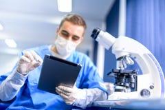 Farmacéutico que trabaja en los medicamentos de venta con receta con la tableta moderna Imágenes de archivo libres de regalías