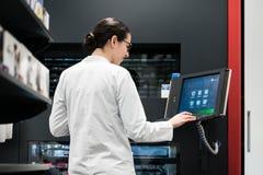 Farmacéutico que usa un ordenador mientras que maneja la acción de la droga en pha Fotos de archivo libres de regalías