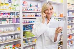 Farmacéutico sonriente en la prescripción de la lectura del teléfono Fotografía de archivo
