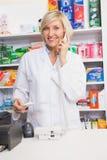 Farmacéutico sonriente en la prescripción de la lectura del teléfono Imagenes de archivo