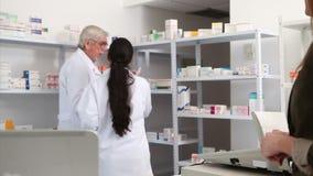 Farmacéutico sonriente que da el papel a un cliente metrajes