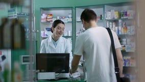 Farmacéutico sonriente que da píldoras del cliente en farmacia almacen de metraje de vídeo