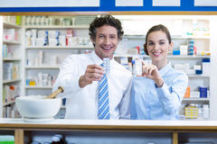 Farmacéutico sonriente que muestra la medicina en farmacia Foto de archivo libre de regalías