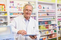 Farmacéutico sonriente que usa la PC de la tableta Imágenes de archivo libres de regalías