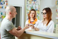 Farmacéutico y cliente en el contador Imagenes de archivo