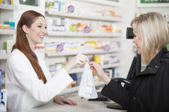 Farmacéutico y cliente en farmacia Imagen de archivo