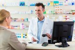 Farmacéutico y cliente en la farmacia foto de archivo