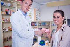 Farmacéutico y cliente sonrientes que discuten un producto foto de archivo libre de regalías