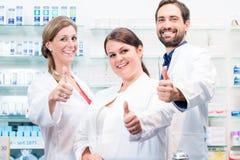 Farmacéuticos en la farmacia que muestra los pulgares para arriba imagen de archivo libre de regalías
