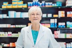 Farmacéuticos mayores experimentados delante de estantes en farmacia imágenes de archivo libres de regalías