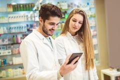 Farmacéuticos que usan la tableta digital mientras que comprueba la medicina imágenes de archivo libres de regalías