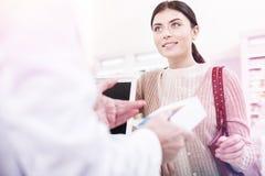 Farmacêutico útil que vende uma cura a um cliente de espera foto de stock