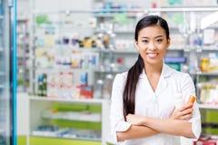 farmacêutico asiático novo alegre com medicamentação que sorri na câmera foto de stock