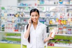 farmacêutico asiático novo de sorriso que fala no smartphone fotos de stock