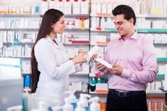 Farmacêutico e homem de consulta na farmácia imagem de stock royalty free