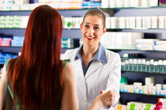 Farmacêutico fêmea em sua farmácia com um cliente Fotos de Stock Royalty Free