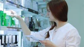 Farmacêutico fêmea novo que seleciona uma medicamentação filme