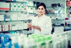 Farmacêutico fêmea que verifica a variedade das drogas na farmácia foto de stock